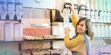 Happy Young Woman Bulk Buying Products for her Food Cupboard by Pouring Grains into a Reusable Container