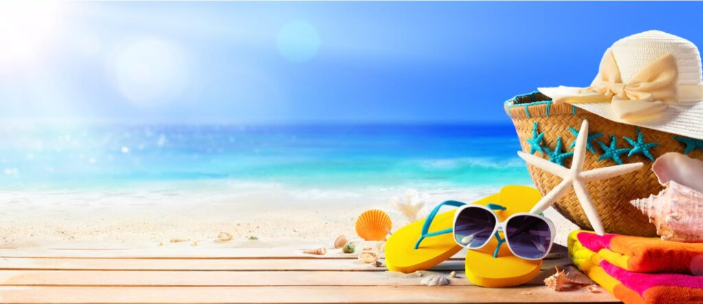 Beach scene with sand, sea and sun. Image of straw sunhat and typical items you take to the beach