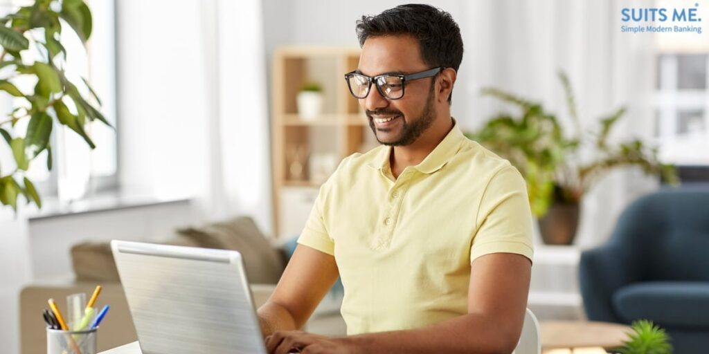 happy south Asian man in glasses with laptop computer finding a current account to suit his needs