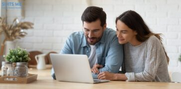 Couple sitting at big wooden table in modern kitchen, looking at laptop screen and managing their money though online banking