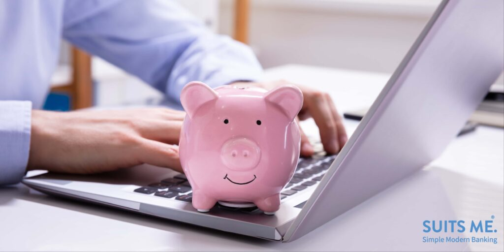 Close-up Of Businessman's Hand Banking On a Laptop With Pink Piggy Bank Representing Savings Account