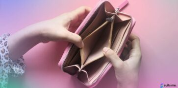 Birds eye view of a woman holding an Empty pink purse on a pink table. No money until payday concept.