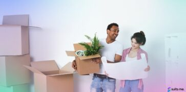Couple moving into their new home in 2021 with their belongings in boxes - renting or buying a home concept