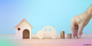 Person Stacking Money Next to an Wooden Toy Car and House. Representing Good Financial Habits